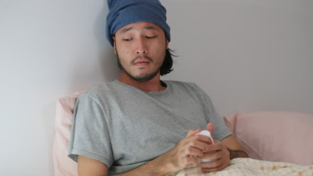 Young asian man taking pill while lying on bed, People healthcare and medical Young asian man taking pill while lying on bed, People healthcare and medical painkiller stock videos & royalty-free footage