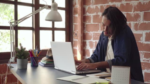 若いアジア人が電話で話し、ビジネスクリエイティブデザイナーのためにラップトップで働く - パソコン 日本人点の映像素材/bロール