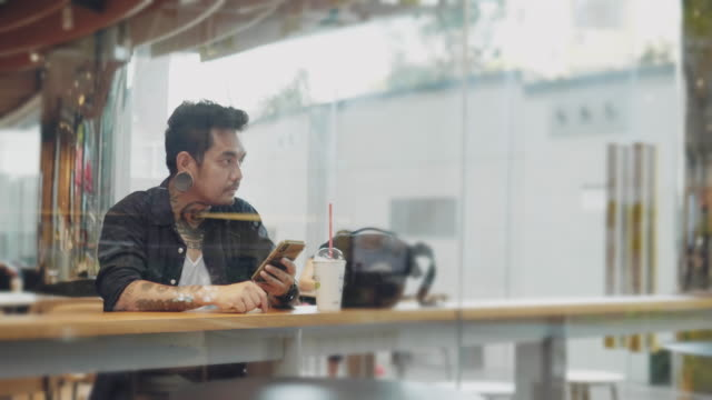 young asian man texting with smartphone at cafe table - solo un uomo giovane video stock e b–roll