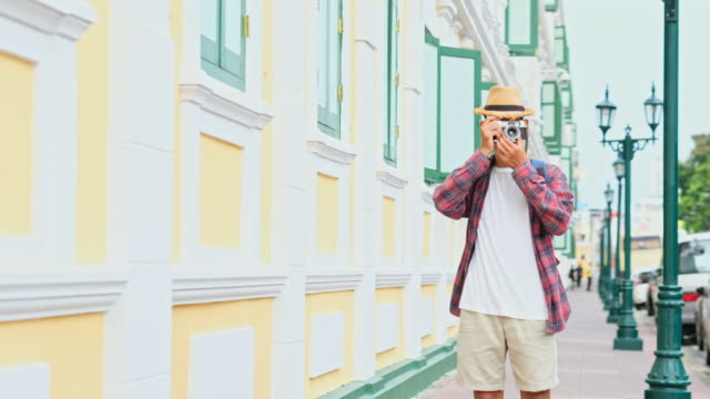 Young asian man tourist holding camera for photographing while travel along the city street, Teenage backpacker on journey in summer vacation in asia
