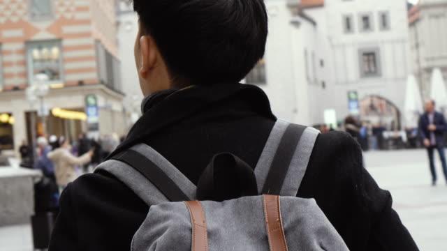 молодой азиатский турист, путешествующий по центру города в европе. мужской турист гуляет по площади мариенплац, мюнхен, германия - турист с рюкзаком стоковые видео и кадры b-roll