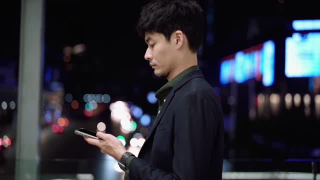 ung asiatisk man som använder smart telefon på nattgatan - telefonmeddelande bildbanksvideor och videomaterial från bakom kulisserna