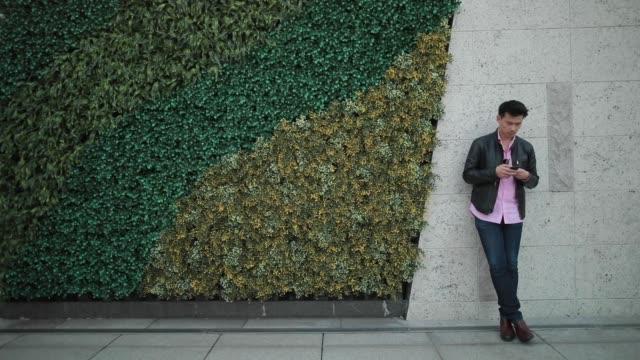 vídeos de stock e filmes b-roll de young asian man using smart phone on street - homem casual standing sorrir