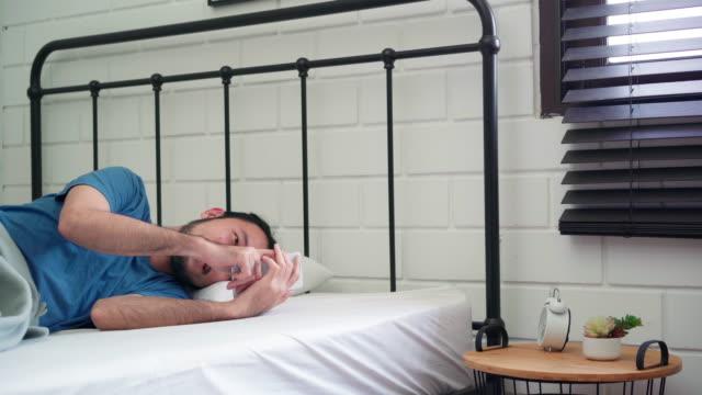 vídeos y material grabado en eventos de stock de joven asiático se despierta por la mañana, asia macho usando el teléfono móvil comprobar las redes sociales y enviar un mensaje después de despertar en la cama en el dormitorio en casa. hombres guapos siesta, sueño relajarse en el concepto de casa mo - acostado