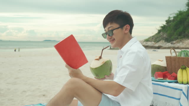 Young Asian man wear sunglasses is relaxing with reading a book in the white sand beach and near sea with tropical fruit in background. Summer, holidays, vacation and happy people in Thailand concept.