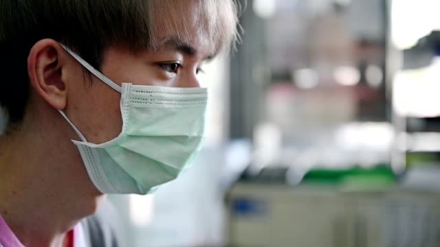 Young asian man wearing medical face mask with coughing
