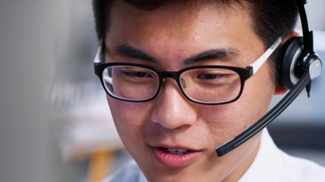 young asian man working in a call centre, close up - cuffia attrezzatura per l'informazione video stock e b–roll