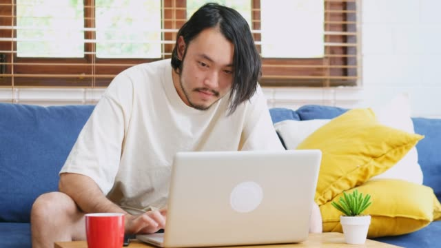 young asian man working with laptop computer while sitting on sofa at home living room, people and technology, working at home, online education - sud est asiatico video stock e b–roll