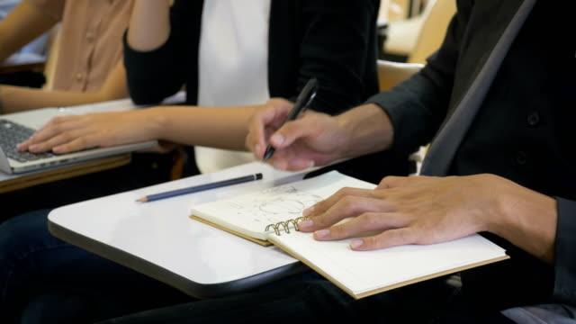 vídeos de stock, filmes e b-roll de young asian homem escrevendo no caderno e fazer pesquisas na biblioteca da faculdade ou sala de aula, aprendendo a educação e o conceito de escola - aula de redação