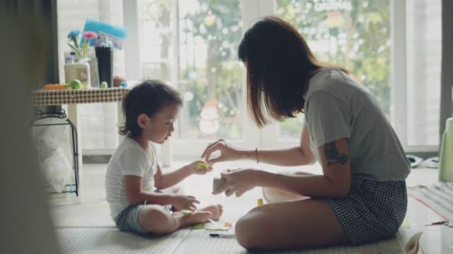 年輕的亞洲母親和兒子用紙工藝製作玩具 - 手工藝 個影片檔及 b 捲影像