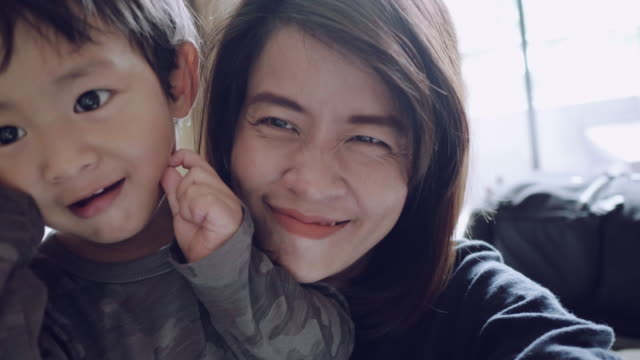 pov : young asian mother and son taking self portrait. - video call video stock e b–roll