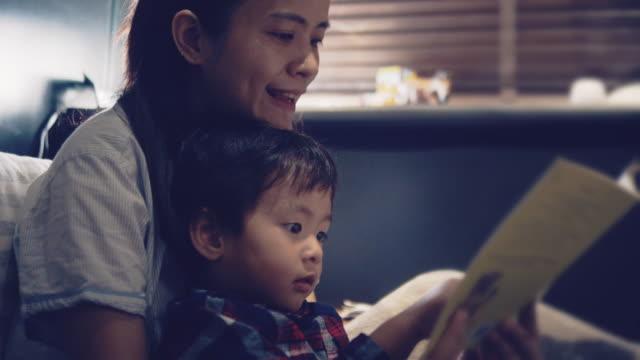 unga asiatiska mamma läser hennes son en god natts aga - cosy pillows mother child bildbanksvideor och videomaterial från bakom kulisserna