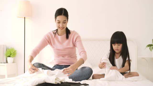 若いアジアの母親は、彼女の小さな娘に服を折りたたんで教えています。母と娘は家事を手伝っています。 - 楽しい 洗濯点の映像素材/bロール