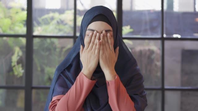 stockvideo's en b-roll-footage met jonge aziatische moslimvrouw die tot god bidt. - koran