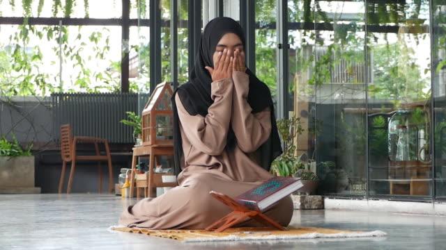 Jovem mulher muçulmana asiática , lendo livro sagrado , orando e prostrando , orando tempo namaj - vídeo