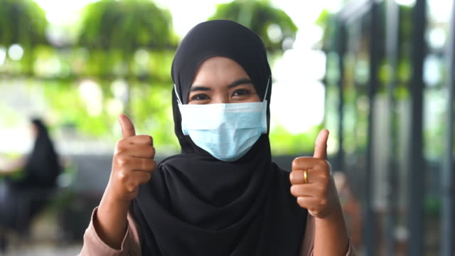 Young Asian Muslim Woman with surgical mask protection with good gesturing , thumbs up - vídeo