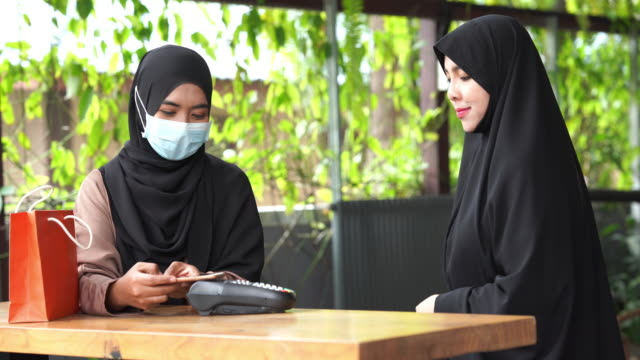 Young Asian Muslim Women online shopping , contect payment  with mobile app technology , Ramadan at home - vídeo