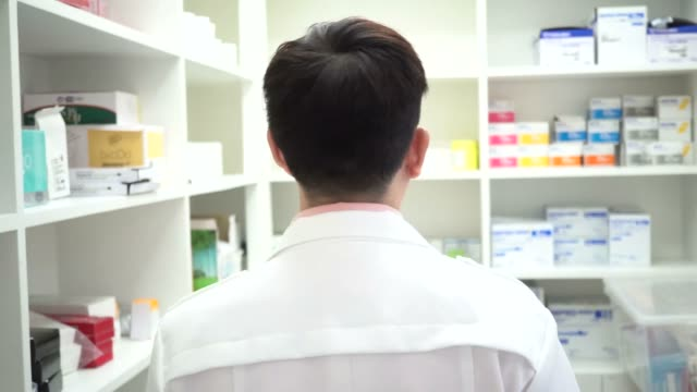 Young Asian pharmacist walking and checking drugs at drugstore room Young Asian pharmacist walking and checking drugs at drugstore room storage room stock videos & royalty-free footage