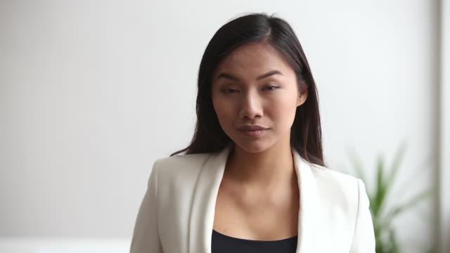 junge asiatische berufsgeschäftsfrau schaut in die kamera im büro - weibliche angestellte stock-videos und b-roll-filmmaterial