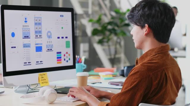 現代のクリエイティブオフィスでコンピュータデスクトップ上のモバイルアプリをコーディング若いアジアのプログラマーの男, ビジーアジアux, uiデザイン開発者, アジアクリエイティブ男性 - クリエイティブな職業点の映像素材/bロール