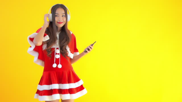Young asian santa woman with many action on yellow isolated background