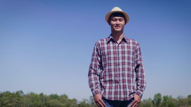 Young Asian smiling man or farmer looking at camera in cultivated field