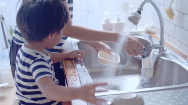 Young asian woman and baby boy washing dishes in kitchen.