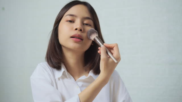 Young Asian woman applies makeup on the face.