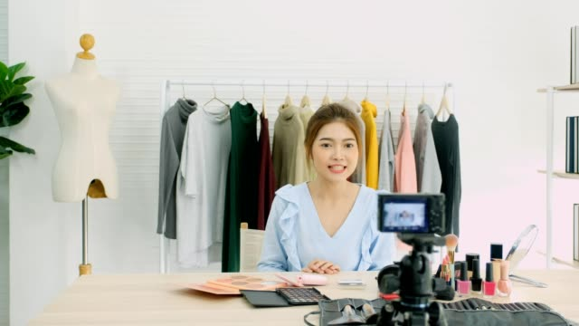 young asian woman beauty blogger showing cosmetic while recording how to make up video tutorial by camera, vlog concept, beauty and fashion people and technology communication - influencer filmów i materiałów b-roll