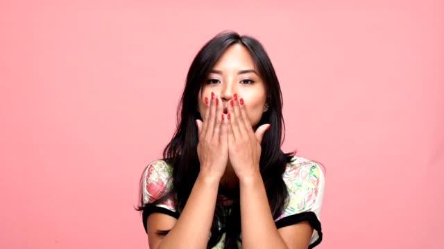 ung asiatisk kvinna blåser kyssar över rosa bakgrund. - blåsa en kyss bildbanksvideor och videomaterial från bakom kulisserna