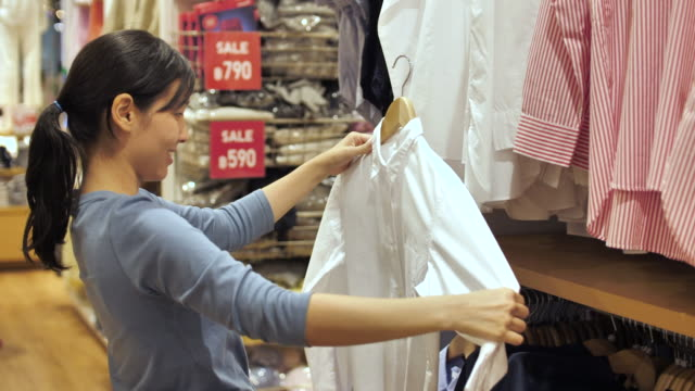 Young Asian woman browsing in the fashion Clothes store