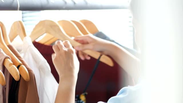 vídeos y material grabado en eventos de stock de mujer asiática joven navegando en la tienda de moda. foto de primer plano. - vestimenta