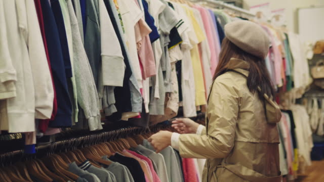 Young asian woman chooses clothes at rack in shopping mall