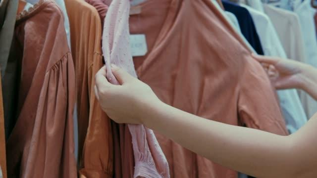 vídeos de stock, filmes e b-roll de jovem mulher asiática escolhe roupas na loja do centro comercial - boutique
