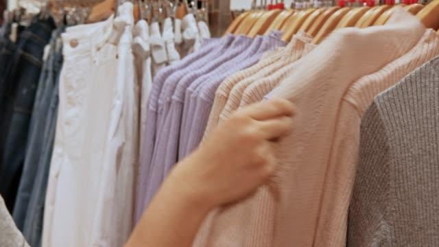 vídeos y material grabado en eventos de stock de mujer asiática joven elige ropa en centro comercial de la tienda - moda playera