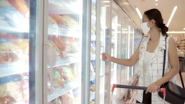 junge asiatische frau auswahl und kommissionierung produkt aus tiefkühltruhe im supermarkt mit gesichtsmaske schutz vor staub und virus für gesund. - gefrierkost stock-videos und b-roll-filmmaterial