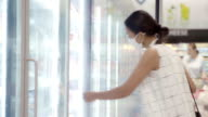 istock Young Asian Woman Choosing and Picking Product from Deep Freezer in Supermarket Store with  Face Mask Protection from Dust and Virus for Healthy. 1210670466