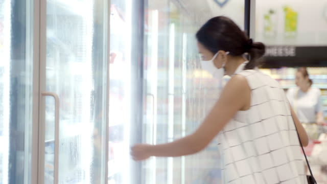 young asian woman choosing and picking product from deep freezer in supermarket store with  face mask protection from dust and virus for healthy. - замороженные продукты стоковые видео и кадры b-roll