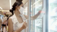 istock Young Asian Woman Choosing and Picking Product from Deep Freezer in Supermarket Store with  Face Mask Protection from Dust and Virus for Healthy. 1210679563