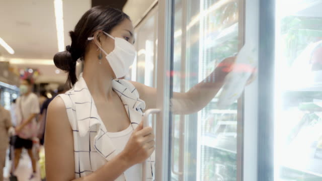 Young Asian Woman Choosing and Picking Product from Deep Freezer in Supermarket Store with  Face Mask Protection from Dust and Virus for Healthy. Young Asian Woman Choosing and Picking Product from Deep Freezer in Supermarket Store with  Face Mask Protection from Dust and Virus for Healthy. grocery aisle stock videos & royalty-free footage