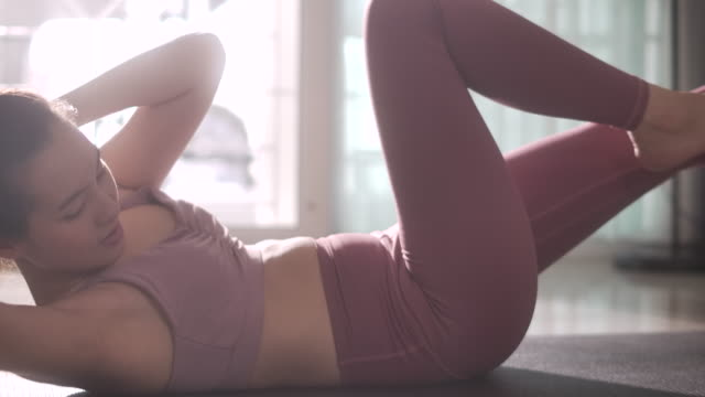 young asian woman doing cardio crisscross exercise for abs lying on sports mat indoors, slow motion - decolleté video stock e b–roll