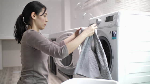 Young Asian woman doing laundry at home