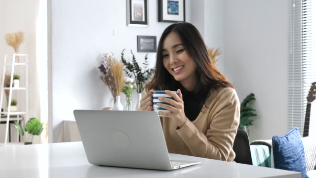 Young Asian woman drinking coffee and using laptop, Working from Home video