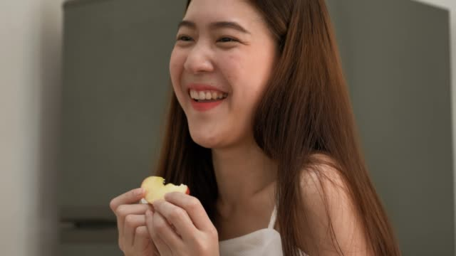 Young asian woman eating apple