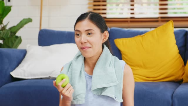 Young asian woman eating green apple after exercising at home living room, People and healthy lifestyles, wellbeing