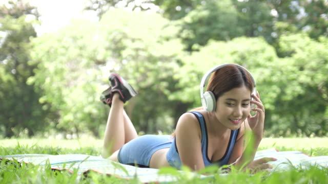 Jóvenes de Asia mujer disfrutando de música en jardín, lenta - vídeo