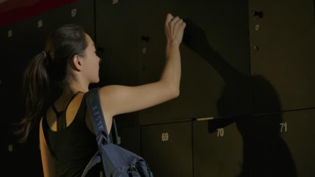 vídeos de stock, filmes e b-roll de jovem mulher asiática vestiário a entrar no ginásio, tomando a toalha do armário, em seguida, ir embora para começar a treinar. - armário com fechadura