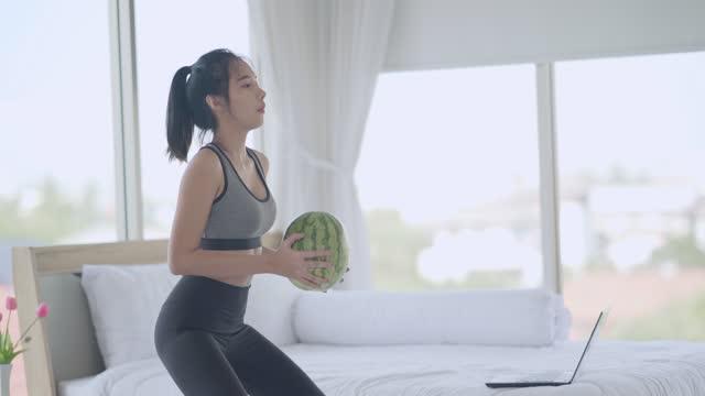 giovane donna asiatica esercizio con anguria a casa con l'aiuto di tutorial online in camera da letto - braccio umano video stock e b–roll
