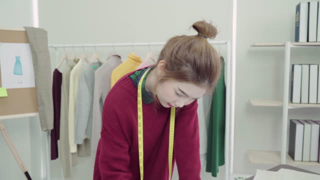 Young Asian woman fashion designer drawing using pencil and looking at paper while working in the workshop studio. video