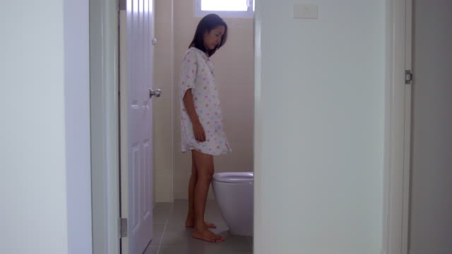 Young Asian Woman Flushing Water Toilet Seat and Walk Out from Toilet Restroom.